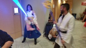 Yuna from Final Fantasy and a random Jedi try out each other's weapons.
