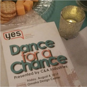 The event program for YES Dance with a Chance, on a table with a votive candle and a plate of cheese and crackers.